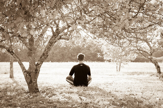a sepia image of a man meditating under some trees represents the best tips for meditation
