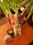 A small statue a candle some rocks and a plant sit on a table to represent healing with feng shui
