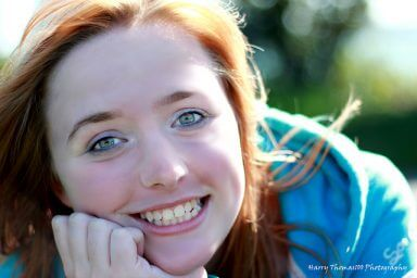 A woman with red hair smiles into the camera happy that she is experiencing radiant recovery
