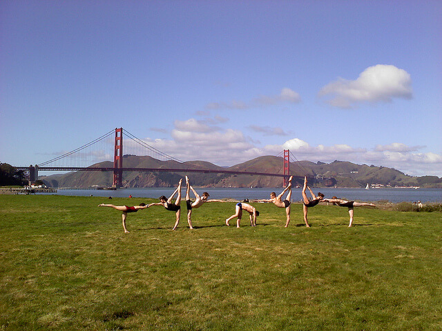 A group of people practicing yoga in front of the Golden Gate bridge probably know some facts about yoga