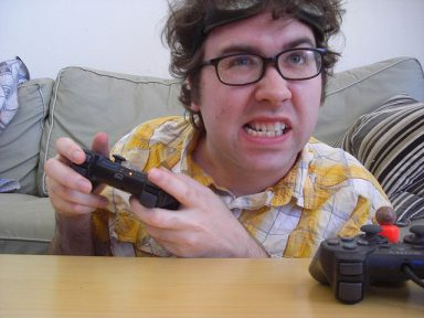 A man makes an aggressive face as he plays a playstation to represent video game addiction