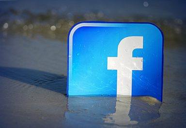 The Facebook logo on a beach represents a place where one can find virtual recovery support