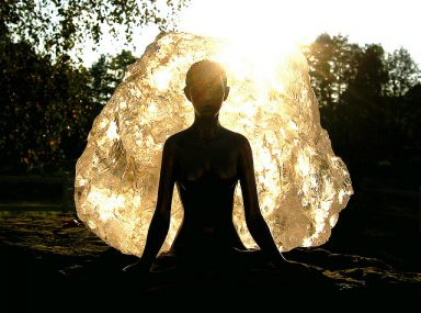 A woman meditates in the woods as she takes advantage of youtube channels for peace